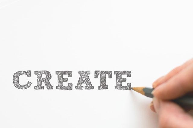 Persona escribiendo con un lápiz la palabra create
